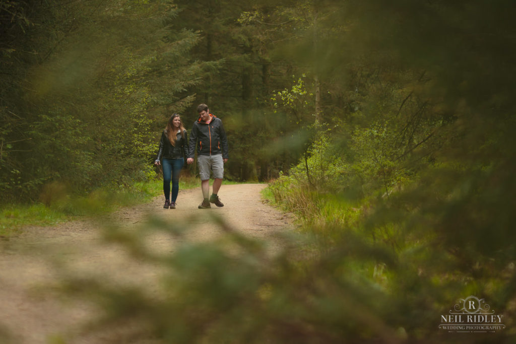 Lancashire Pre Wedding at Beacon Fell, a young couple stroll through the woods on a dirt track