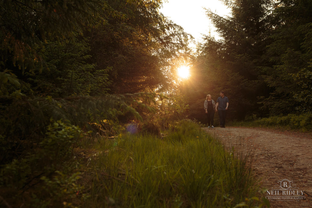 Lancashire Pre Wedding Shoot at Beacon Fell, Young couple walk through a forest at sunset