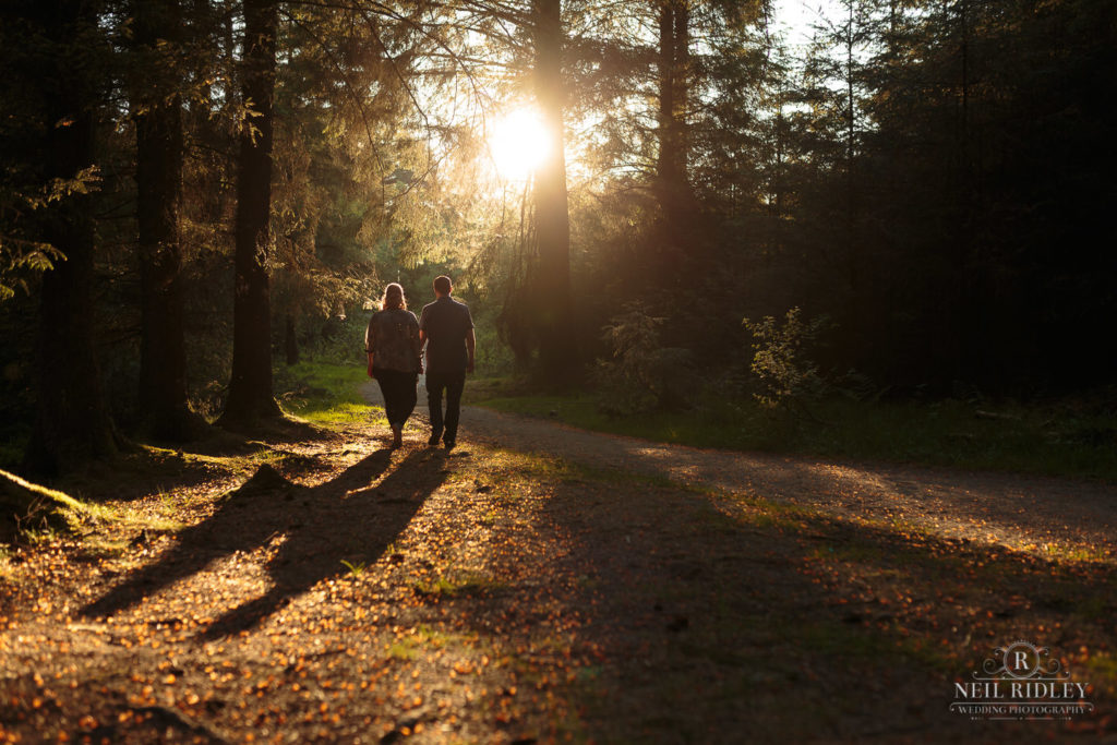Lancashire Pre Wedding Shoot at Beacon Fell, Young couple cast a long shadow whilst walking through a forest