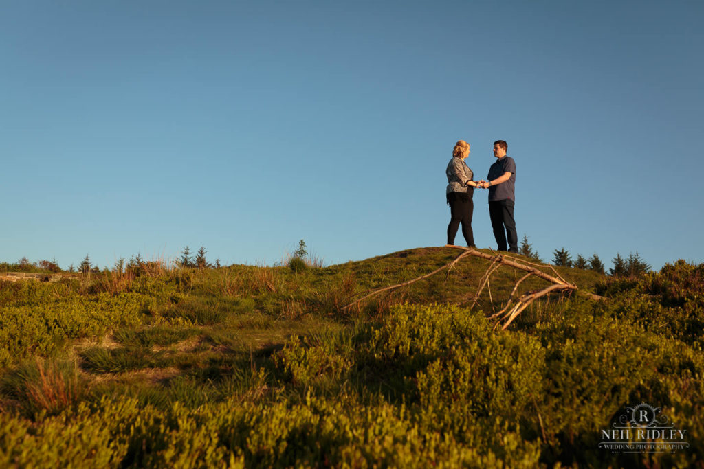 Lancashire Pre Wedding Shoot at Beacon Fell, Young couple hold hands on top of a hill