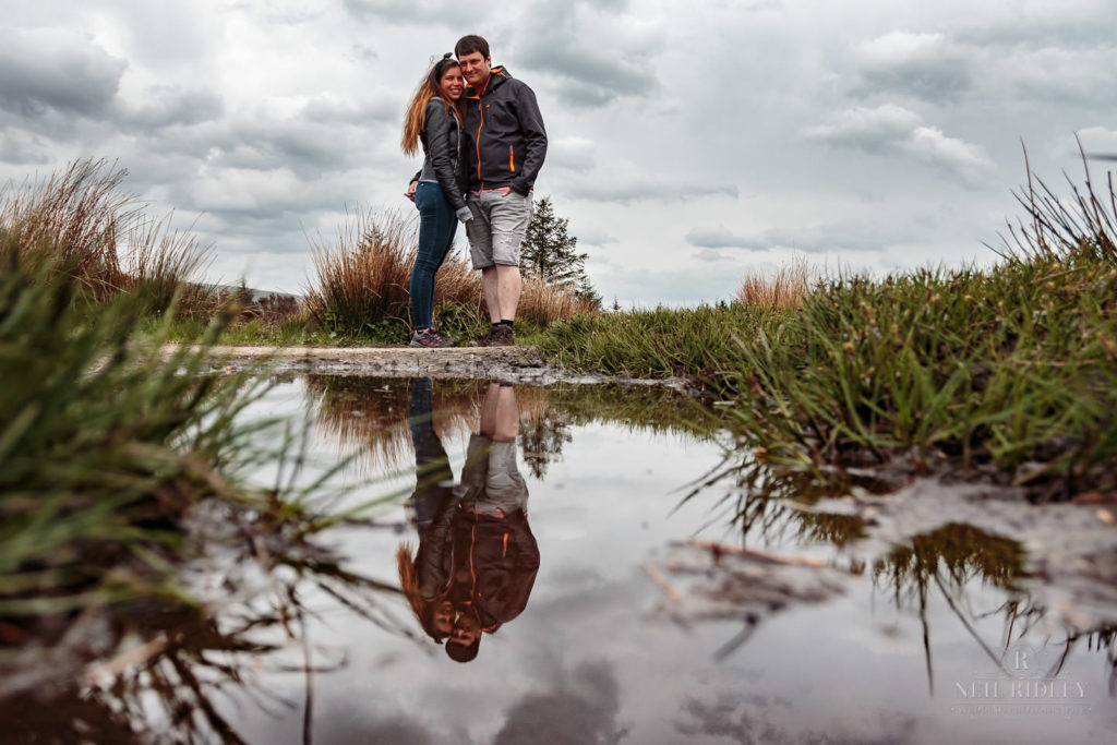 Lancashire Pre Wedding at Beacon Fell, a young couple reflected in a puddle