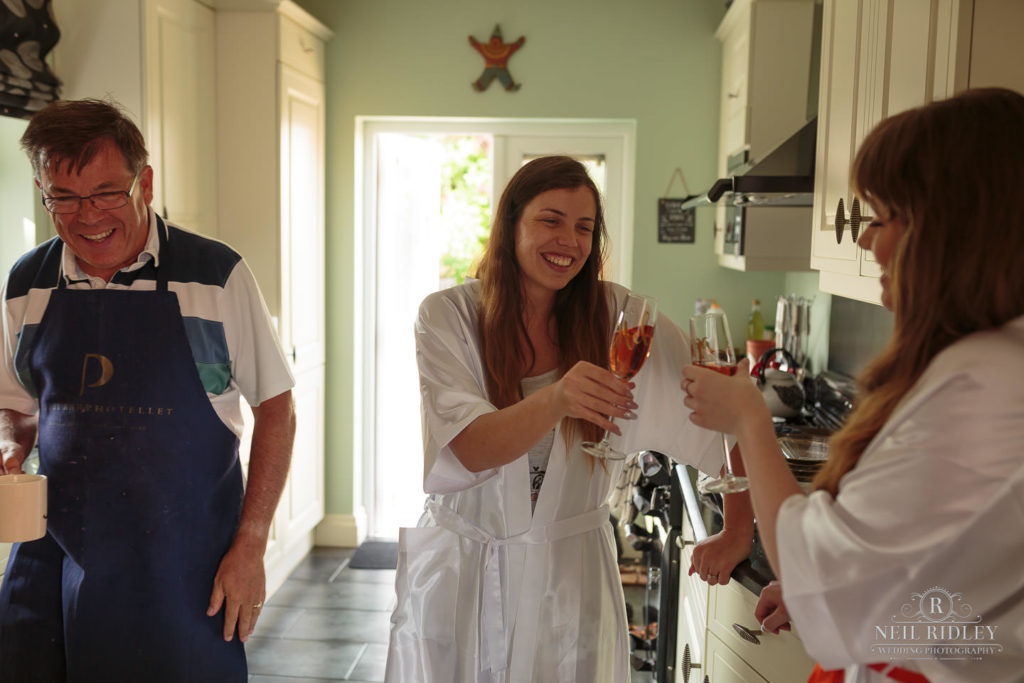 Bride enjoys a glass of champagne in her kitchen during Bridal Prep