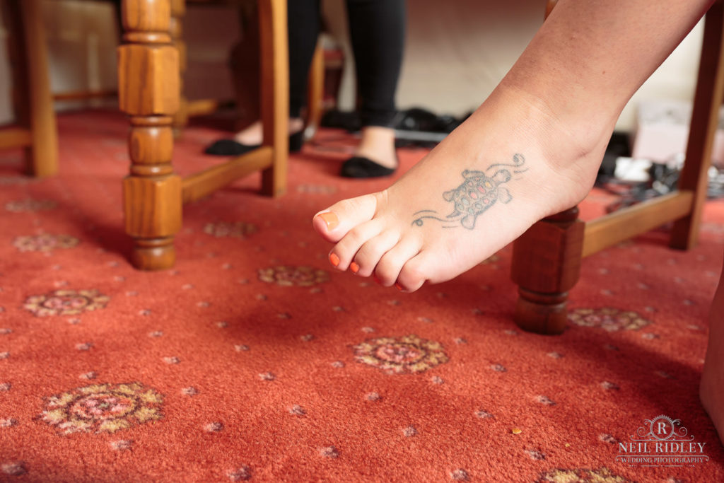 Tattoo of turtle on Bride's foot.