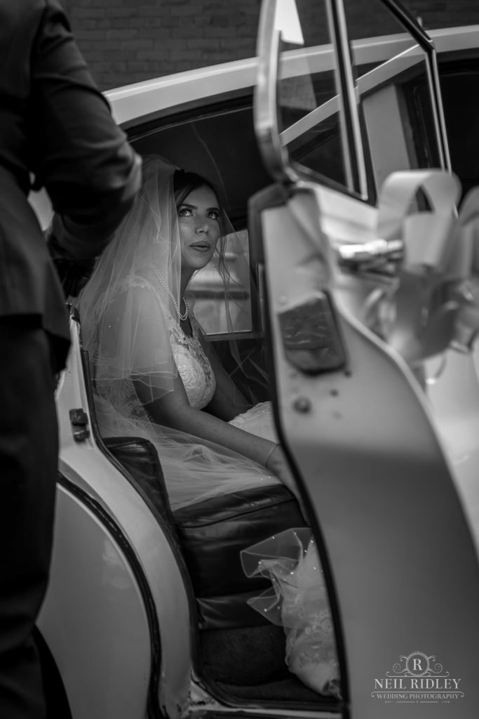 Black and white image of bride in her car at St Thomas Church in St Annes-on-Sea