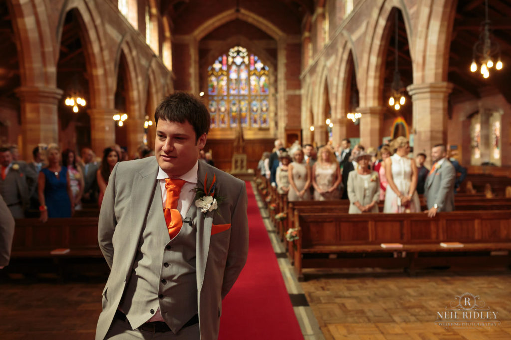 Groom waits at the altar in the church at St Thomas Church in St Annes-on-Sea