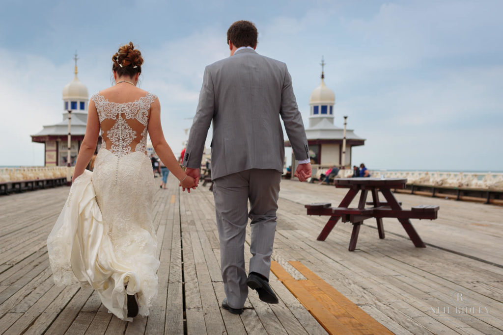 Bride and Groom walk hand in hand on North Pier in Blackpool