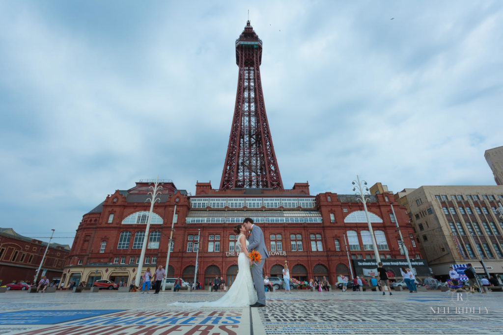 Bride and Groom stand on the Comedy Carpet in front of Blackpool Tower