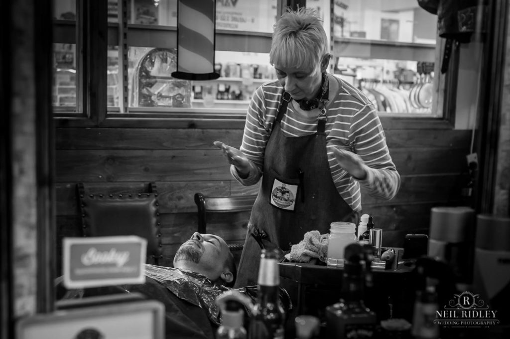 Black and white image of groom having a professional wet shave at Barbers in Bispham.