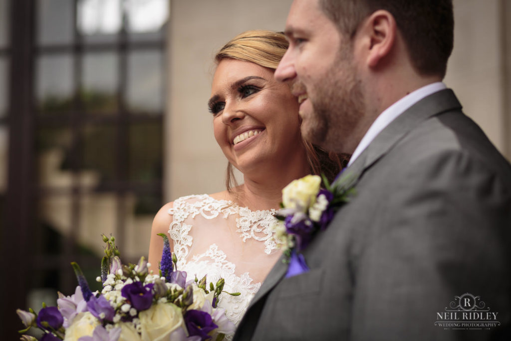 Lancaster Wedding Photographer - Bride and groom Smile for their guests outside Ashton Memorial Lancaster