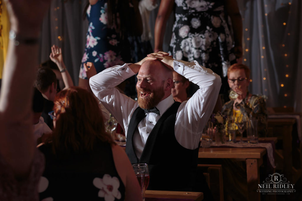 Lancaster Wedding Photographer - Photograph of wedding Guests with hands on his head at Lancaster Brewery
