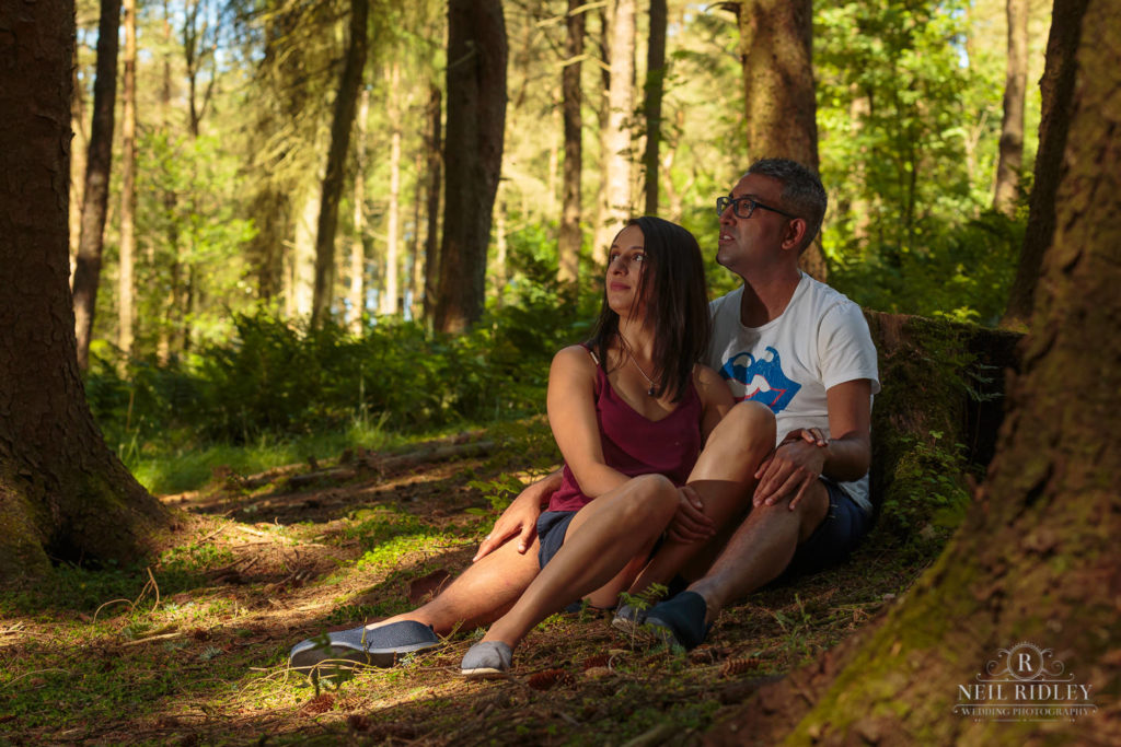 Engagement Shoot Couple sat at the base of a tree in the forest at Beacon Fell Lancashire