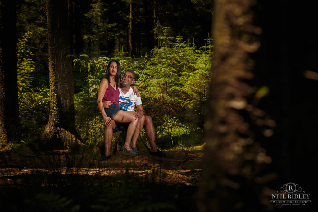 Engagement Shoot Couple sat together on a tree stump in the forest at Beacon Fell Lancashire