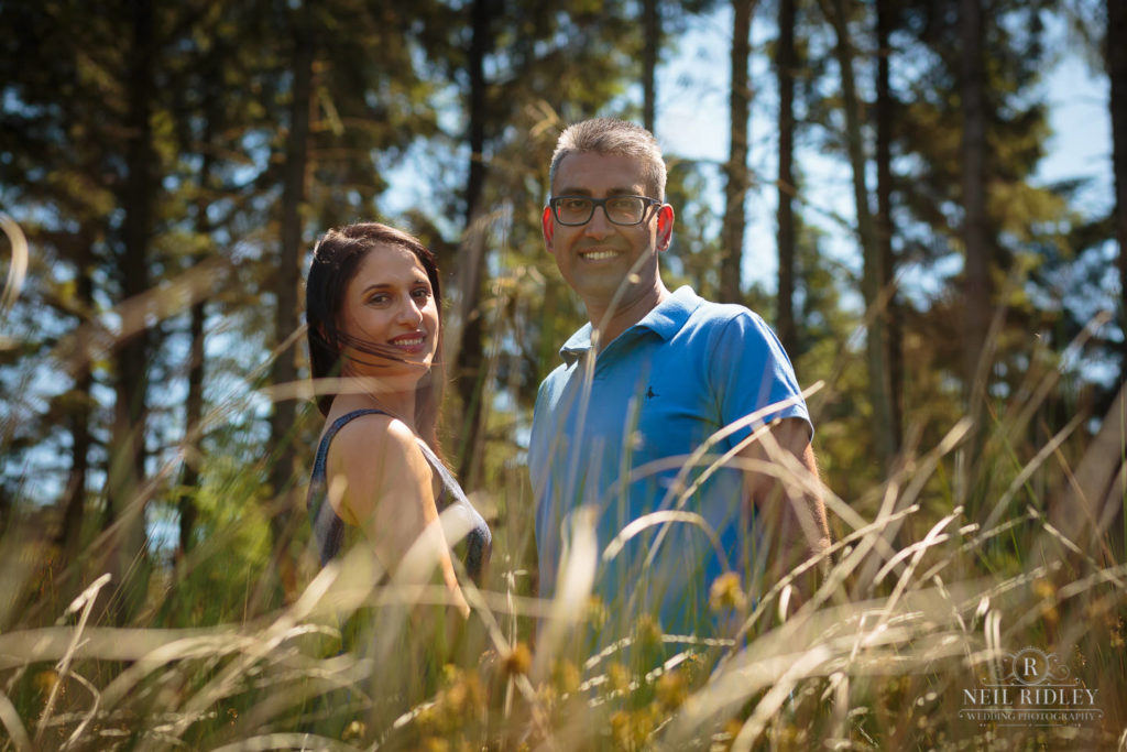 Engagement Shoot Couple look directly at the lens whilst in the forest at Beacon Fell Lancashire