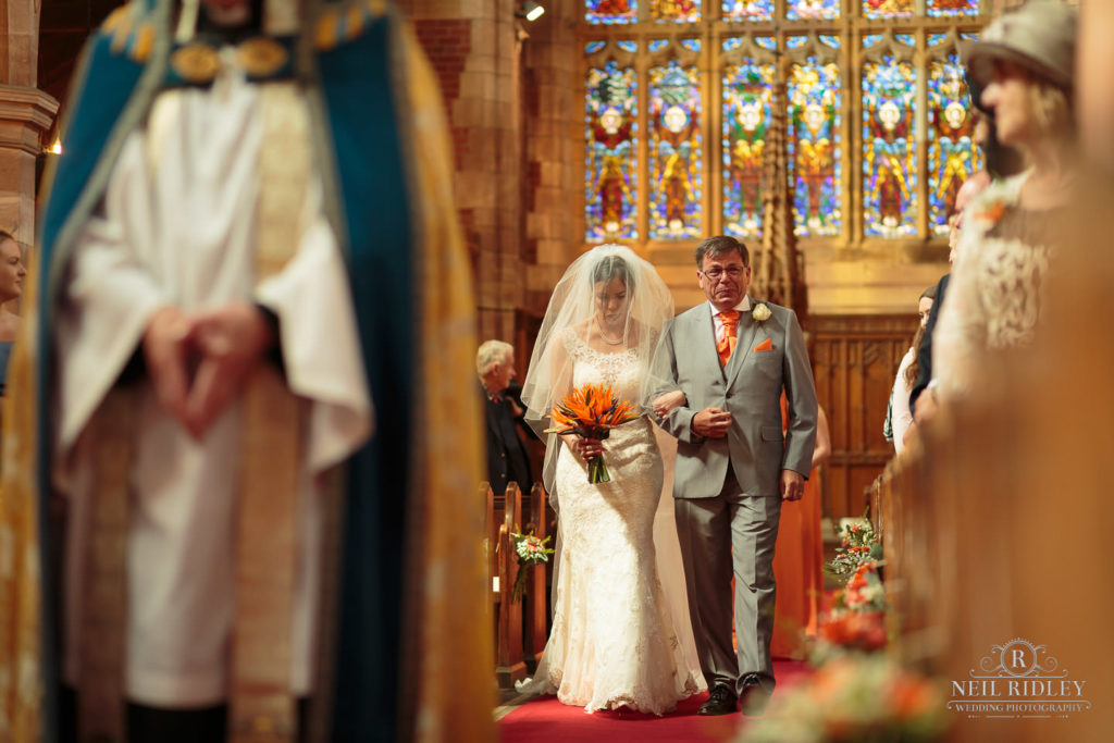 Bride walks down the aisle with her F her father is crying at St Thomas Church in St Annes-on-Sea