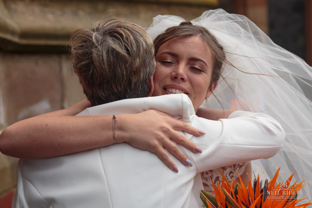 Bride hugs family member outside St Thomas Church in St Annes-on-Sea