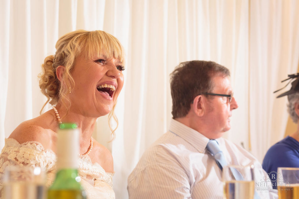 Bride sat at the Wedding Breakfast table laughing at The Park House Hotel, Blackpool