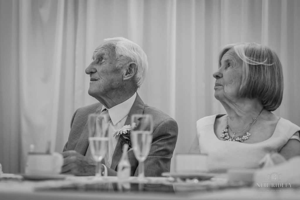 Black and white image of brides parents listening to the speeches at The Park House Hotel, Blackpool