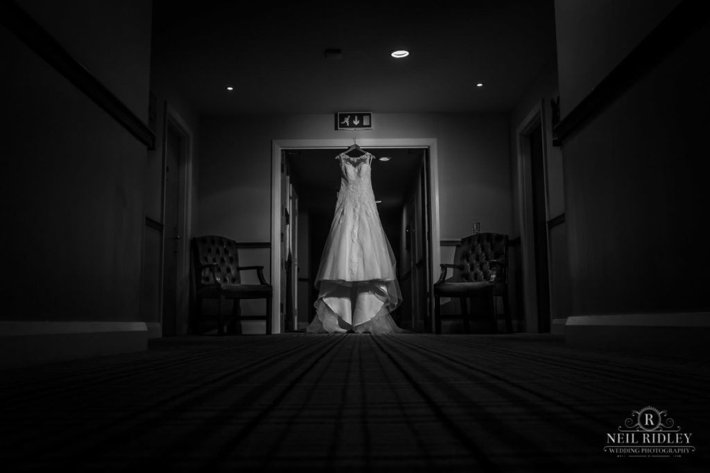 Lancaster Wedding Photographer - Black and White image of Wedding dress hung up in hotel corridor at Lancaster House Hotel