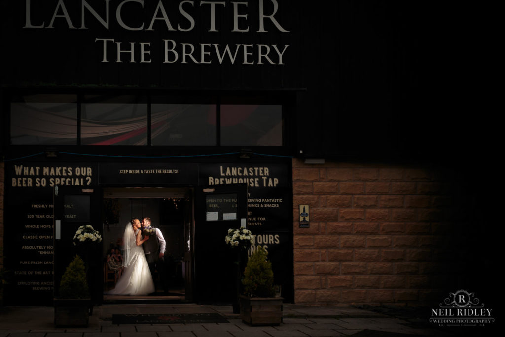 Bride and Groom kissing in entrance at Lancaster Brewery