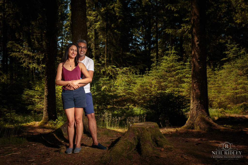 Engagement Shoot Couple stood in sunlight in the forest at Beacon Fell Lancashire