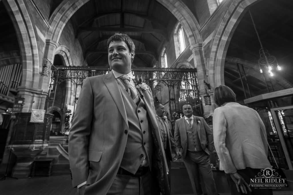 Black and white image of Groom waiting for his for Bride at the church altar at St Thomas Church in St Annes-on-Sea