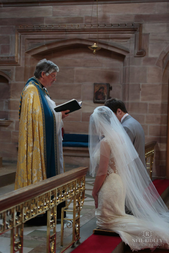 Bride and Groom kneel before the preist during the wedding ceremony St Thomas Church in St Annes-on-Sea