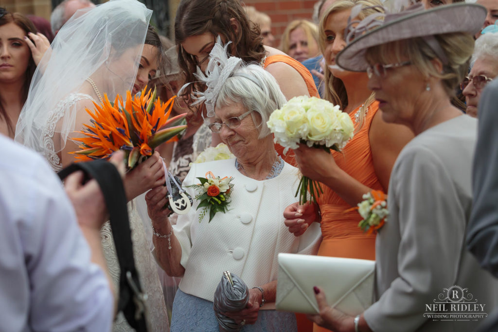 Bride with Family memebers looking at the Bridal Bouquet outside St Thomas Church in St Annes-on-Sea