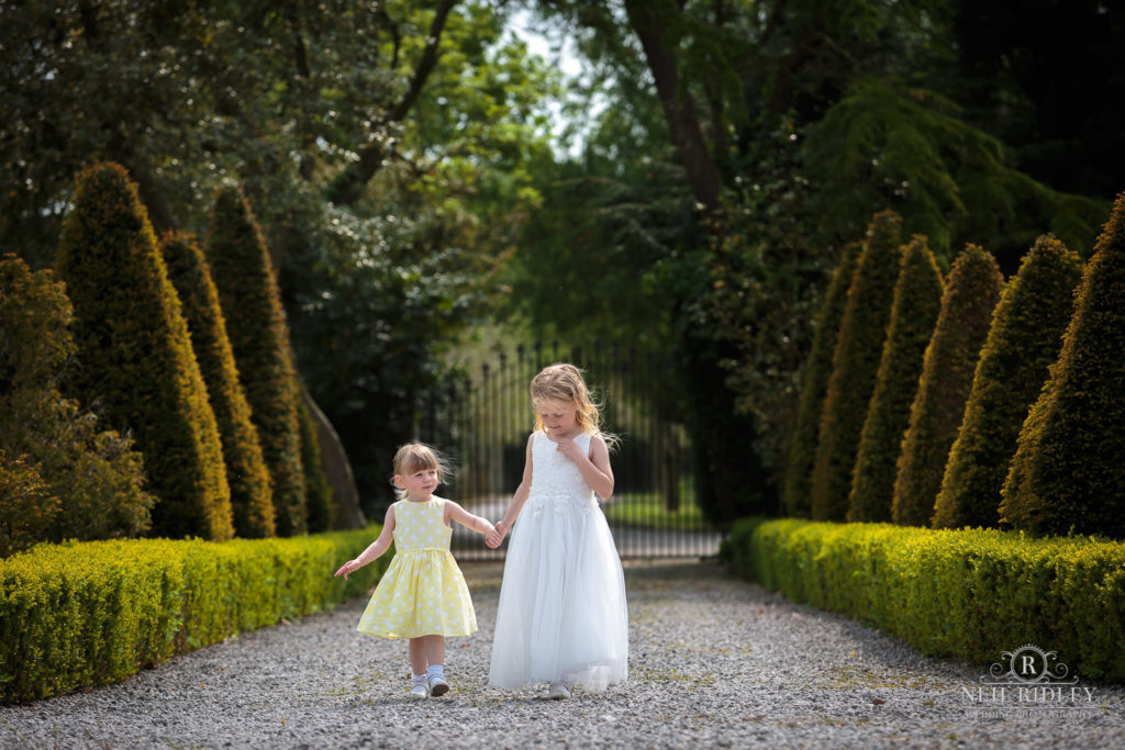 Two little girls walk hand in hand down a tree lined drive at The Great Hall of Mains.