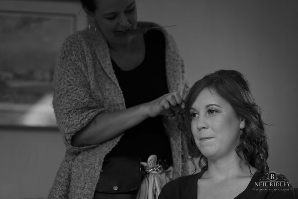 Black and white image of bridesmaid having her hair curled during Bridal Prep