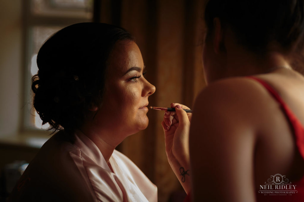 Bridesmaid has her lip stick applied during bridal prep at Macdonald Portal Hotel, Tarporley