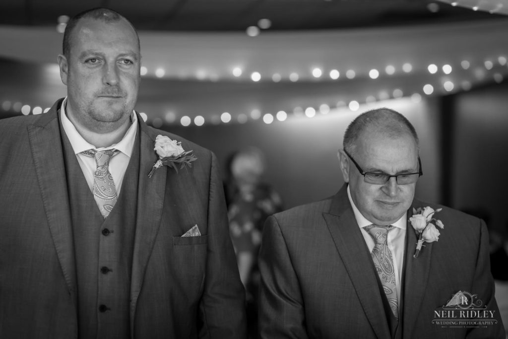 Groom and his best man stand at the alter at Macdonald Portal Hotel, Tarporley