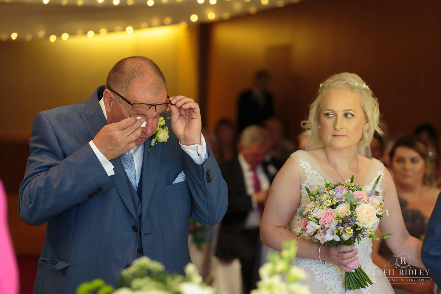 groom wipes his eyes as the bride looks at him at the altar at Macdonald Portal Hotel, Tarporley