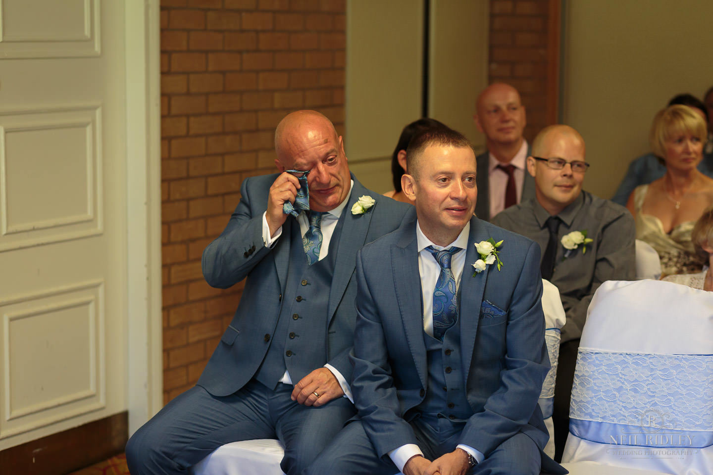 wedding guest wipes his eye at a wedding at Macdonald Portal Hotel, Tarporley