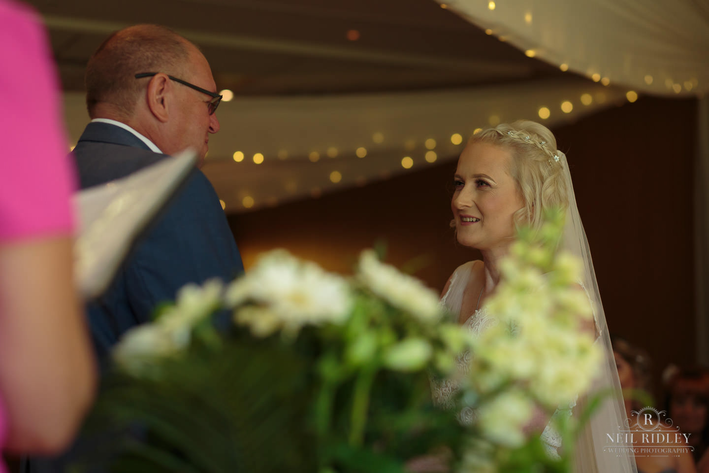 Bride and Groom look at each other whilst exchanging wedding vows at Macdonald Portal Hotel, Tarporley