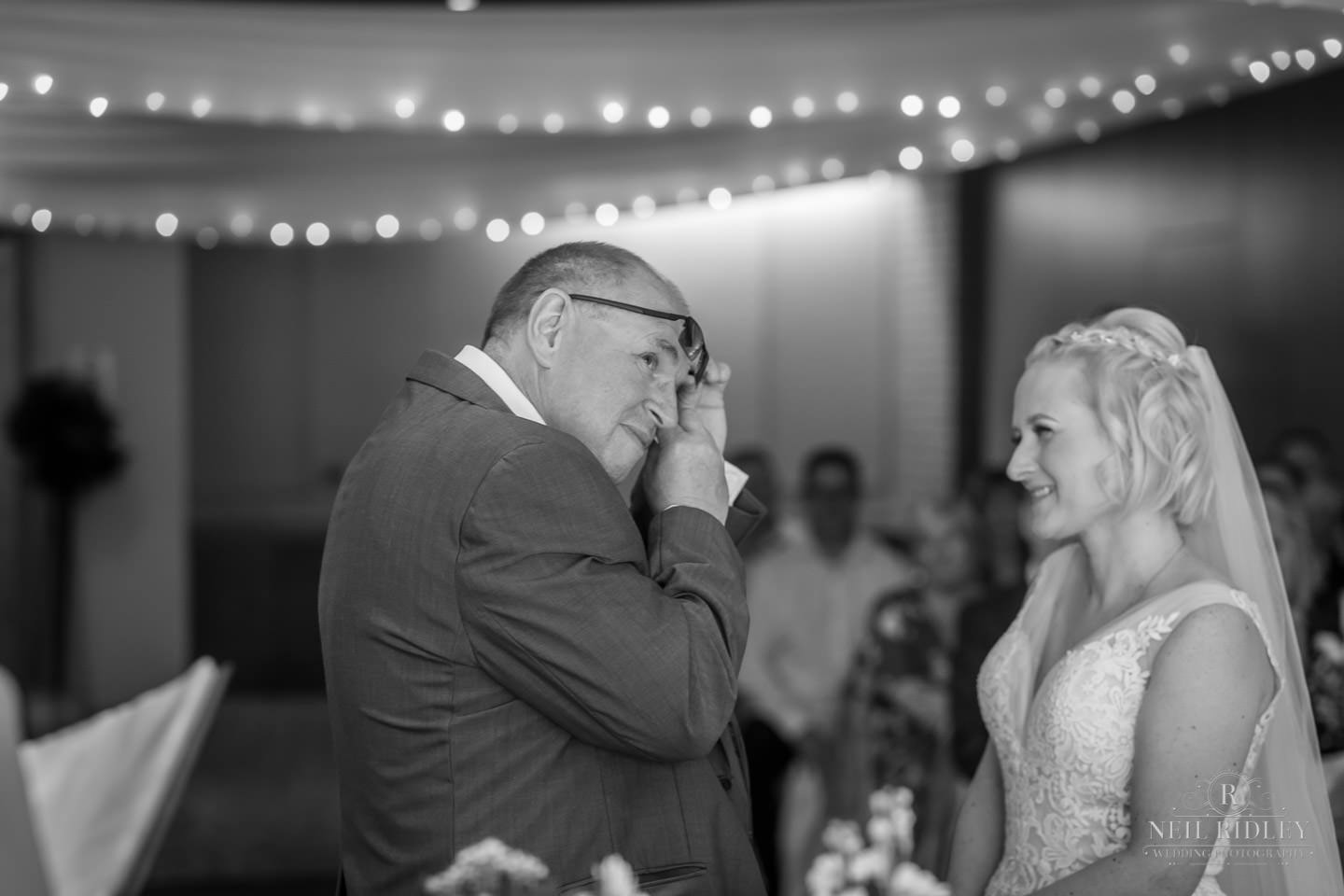 Black and white image of groom wiping his eyes with bride watching him at the altar at Macdonal Portal Hotel, Tarporley