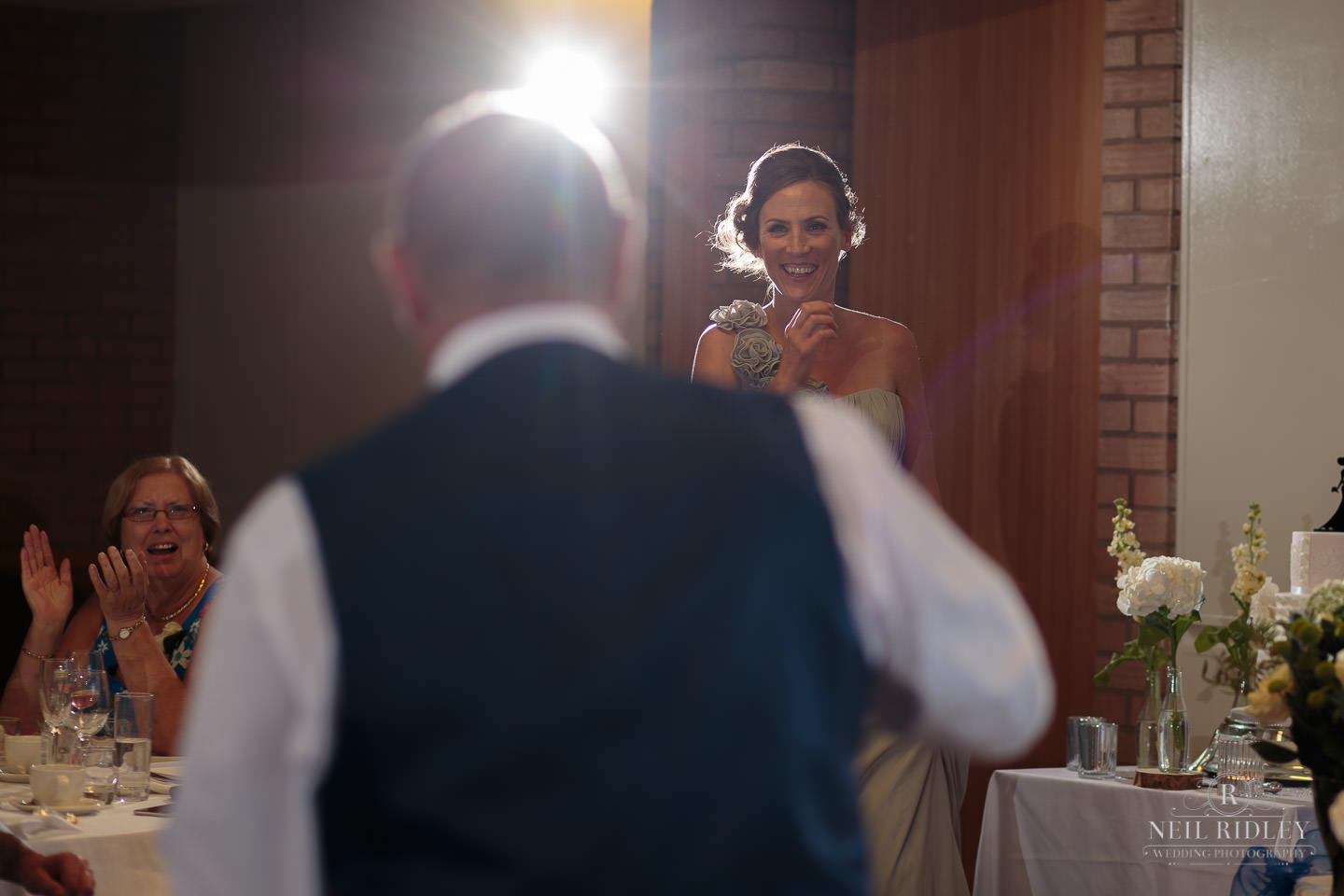 Bridesmaid comes up to recieve a present from the groom during the wedding breakfast at Maccdonald Portal Spa and Hotel