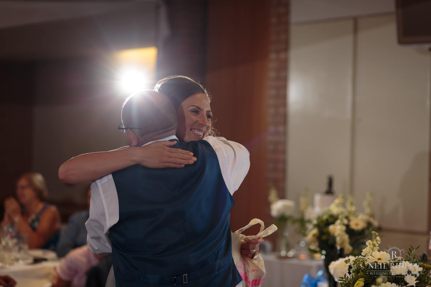 Groom gives bridesmaid a hug during the wedding breakfast at Maccdonald Portal Spa and Hotel