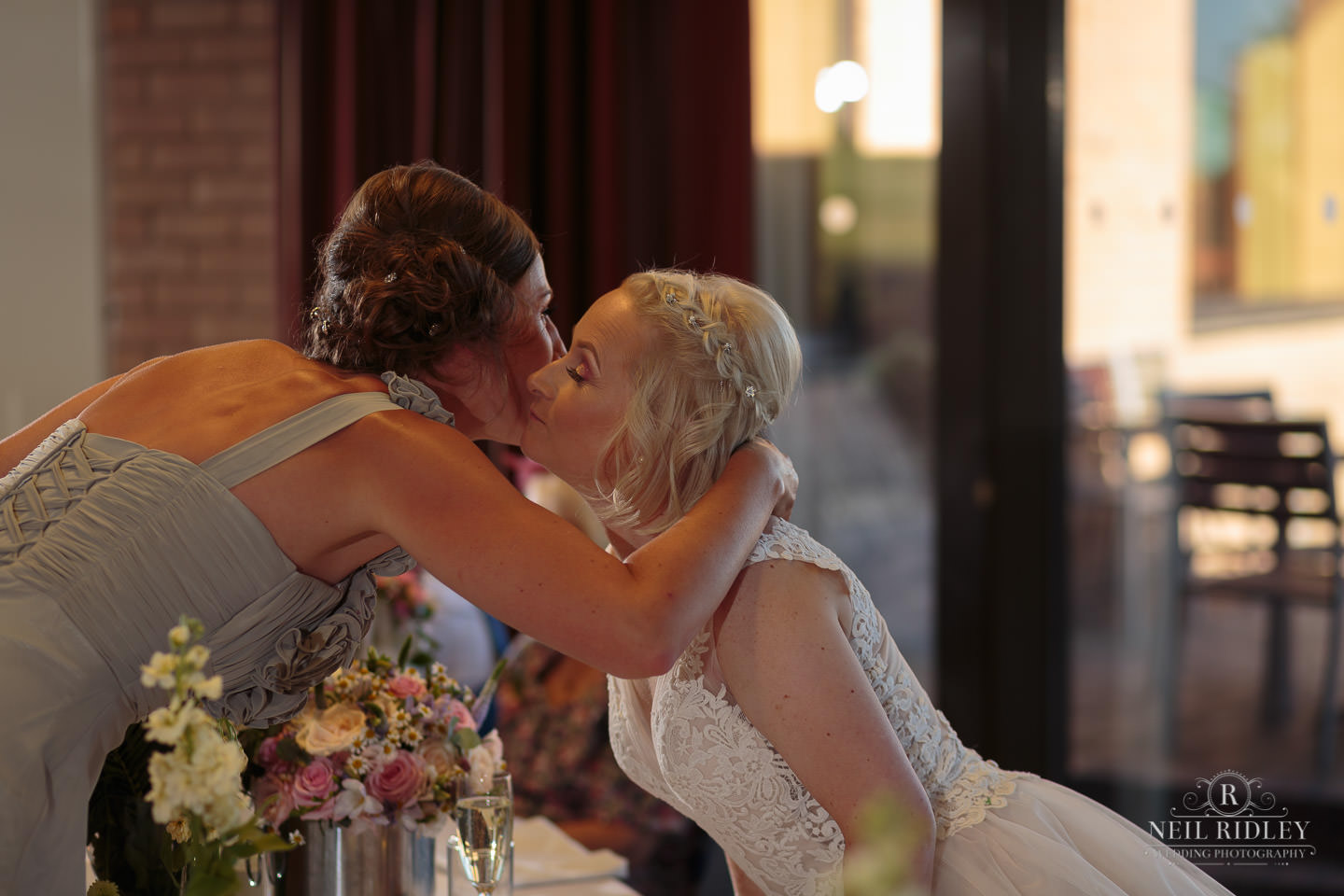 bride hugs her bridesmaid at the top table at Maccdonald Portal Spa and Hotel