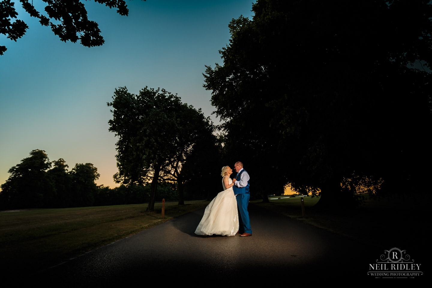 Bride and groom stand in the grounds of Macdonald Portal Hotel, Tarporley with the sunset behind them