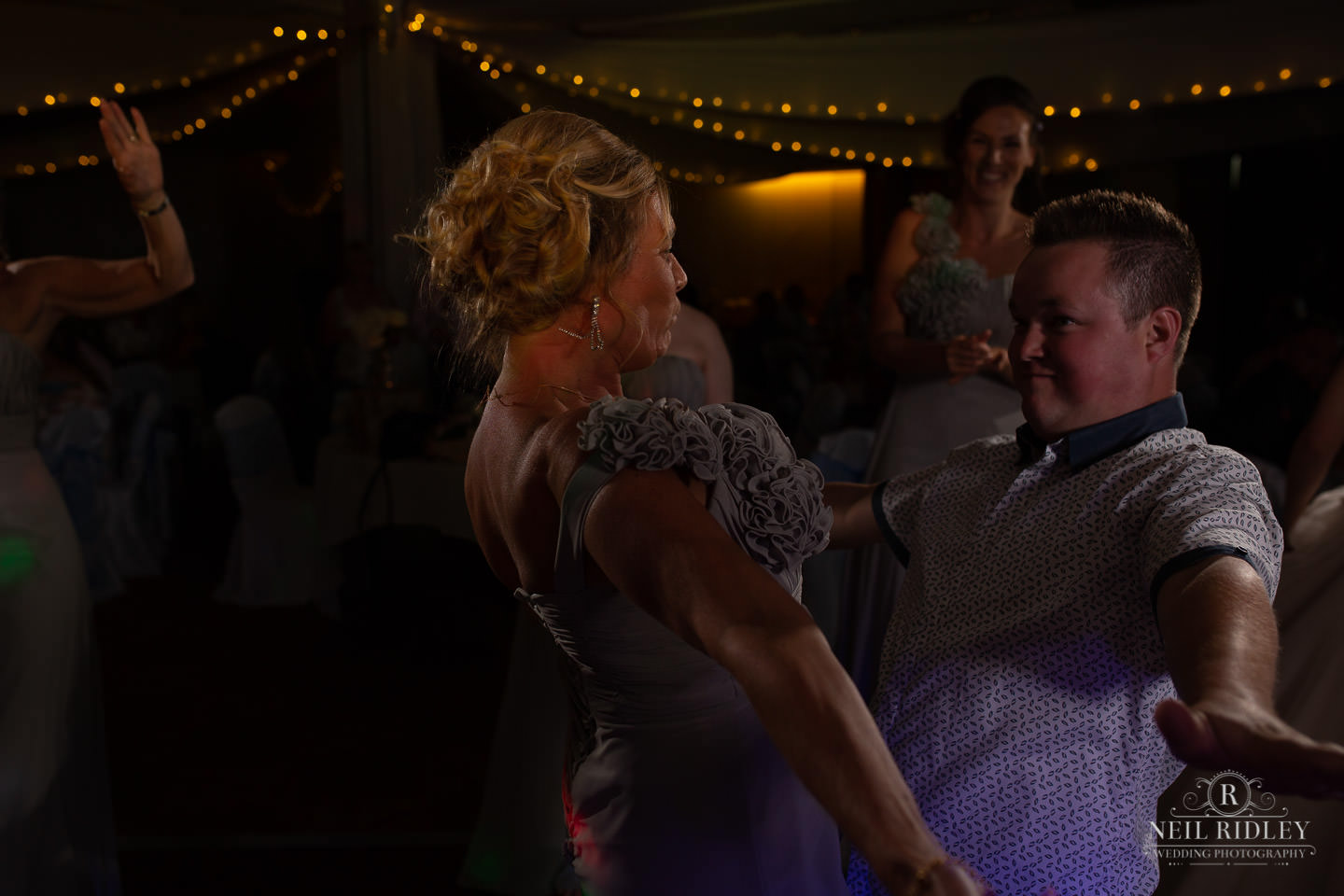 Bridesmaid and guest dance on the dancefloor at Macdonald Portal Hotel in Tarporley