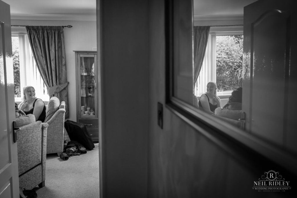 Black and white image of reflections in mirror of Bridal Party during Bridal Prep