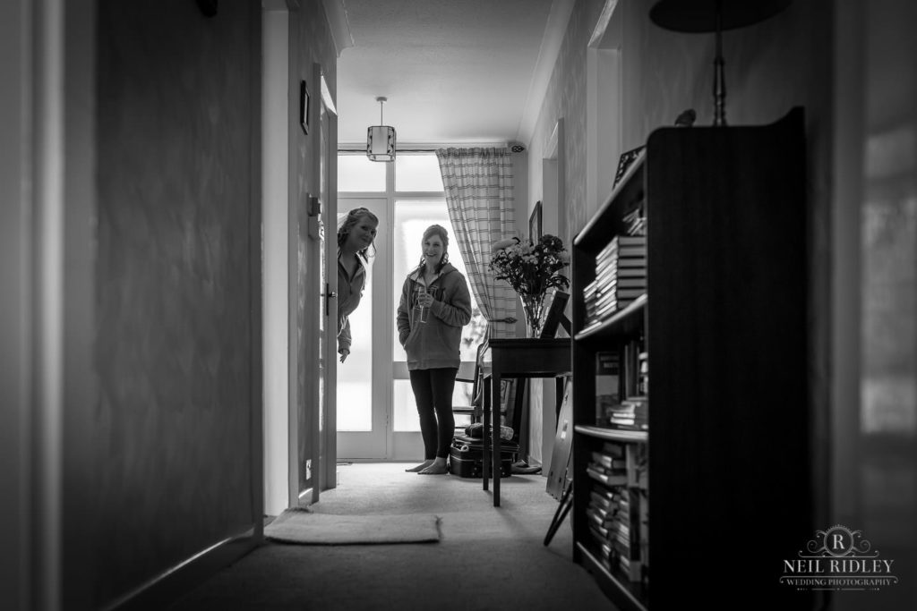 Black and white image of bride and bridesmaid peeking around doorway during Bridal Prep
