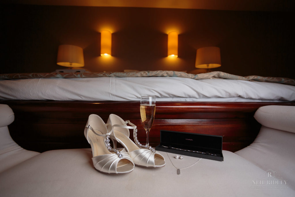 Brides shoes and jewelly at the end of their bed at Garstang Country House Hotel and Golf Club