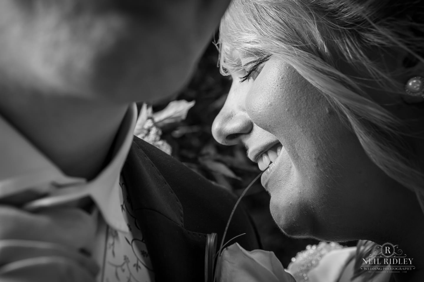 Black and white image of bride smiling with eyes closed with sun on her face
