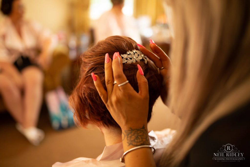 Bridesmaid has hair done during Bridal prep at Macdonal Portal Hotel, Tarporley