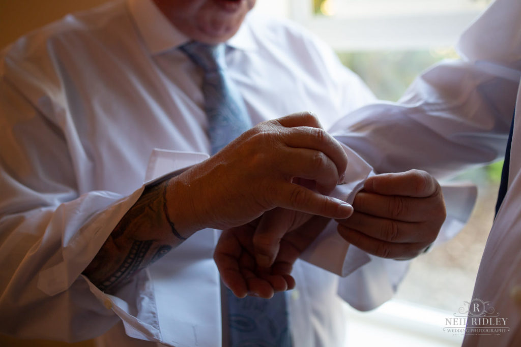 Groom fastens Best Mann's cufflinks during Groom prep at Macdonald Portal Hotel, Tarporley