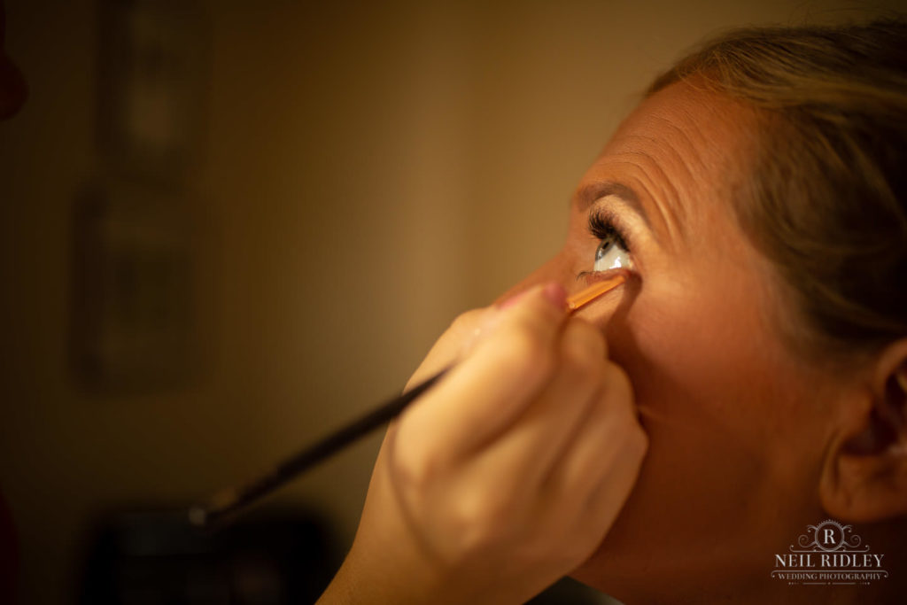 Bridesmaid has her eyeliner applied by Make up artist at Macdonald Portal Hotel, Tarporley