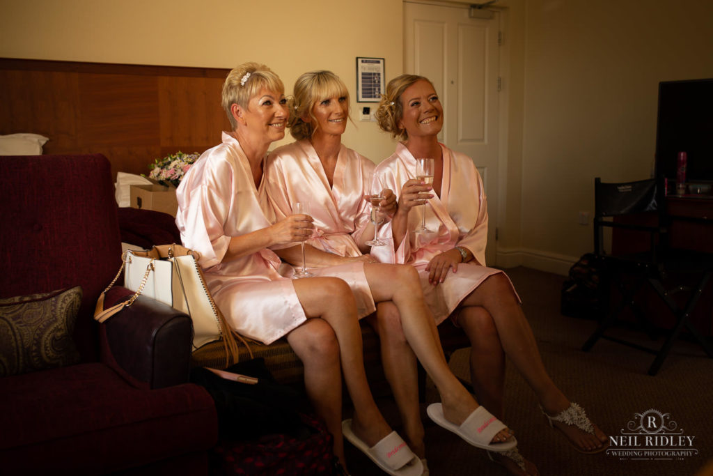 Bridesmaids sit on the bed during bridal prep at the Macdonald Portal Hotel and Sp