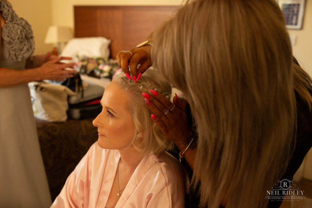 Bride has hair done during bridal prep at Macdonald Portal Hotel, Tarporley