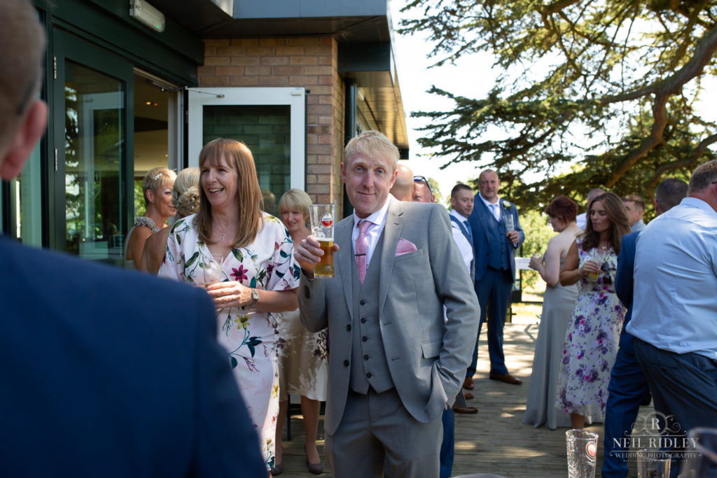 wedding guest stands outside with drink in hand at Macdonald Portal Hotel, Tarporley